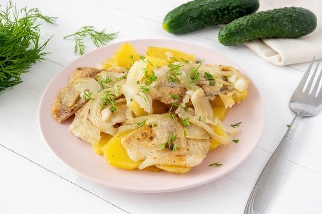 Запеченная рыба и картофель с луком на тарелке на белом деревянном фоне