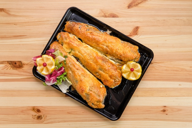 Baked fish in batter on tray