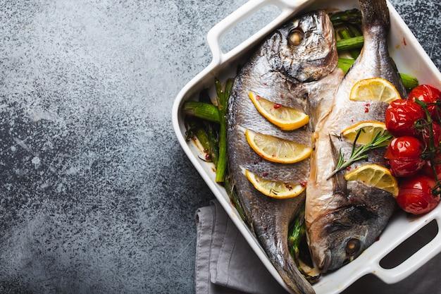 灰色の素朴なコンクリートの背景、上面図に白いセラミックのベーキングパンにグリーンアスパラガスとトマトと焼き魚ドラド。魚のコンセプト、ダイエット、きれいな食事で健康的な夕食