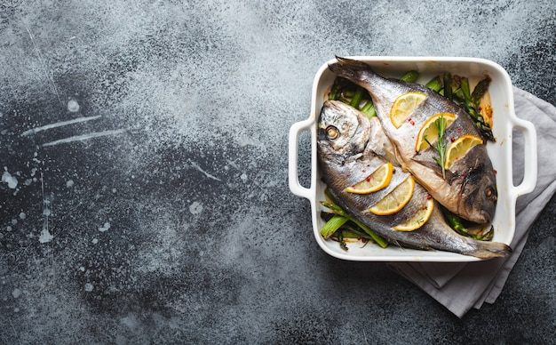 灰色の素朴なコンクリートの背景、上面図に白いセラミックのベーキングパンにグリーンアスパラガスと焼き魚ドラド。魚をコンセプトにしたヘルシーなディナー、ダイエット、きれいな食事。テキスト用のスペース