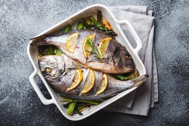 灰色の素朴なコンクリートの背景、上面図に白いセラミックのベーキングパンにグリーンアスパラガスと焼き魚ドラド。魚のコンセプト、ダイエット、きれいな食事で健康的な夕食