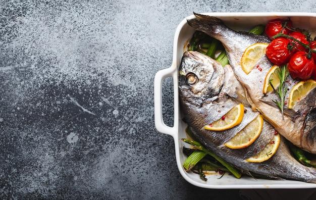緑のアスパラガス、灰色の素朴なコンクリートの背景、上面図に白いセラミックベーキングパンのトマトと焼き魚ドラド。魚をコンセプトにしたヘルシーなディナー、ダイエット、きれいな食事。テキスト用のスペース