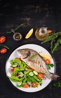 Запеченная рыба дорадо с лимоном и свежим салатом в белой тарелке