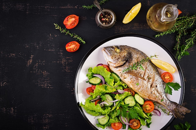 Baked fish dorado with lemon and fresh salad in white plate