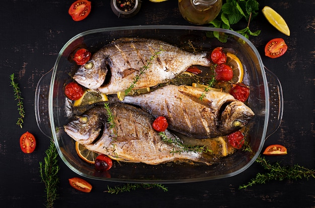 Baked fish dorado with lemon and herbs in baking pan on dark rustic background. top view. healthy dinner with fish concept. dieting and clean eating