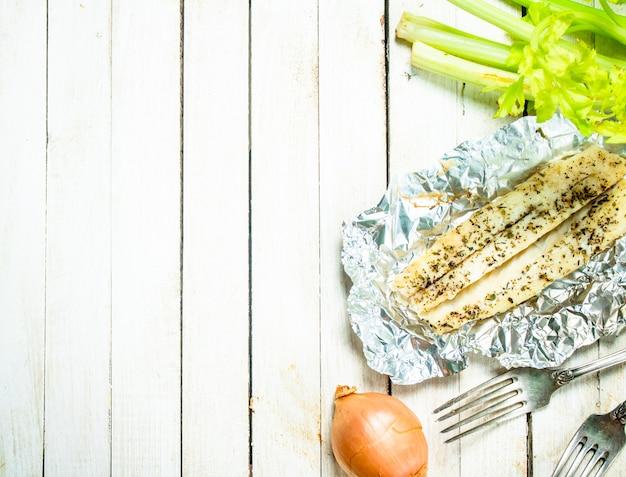 スパイスとセロリを添えた焼き魚の切り身。白い木の背景に。