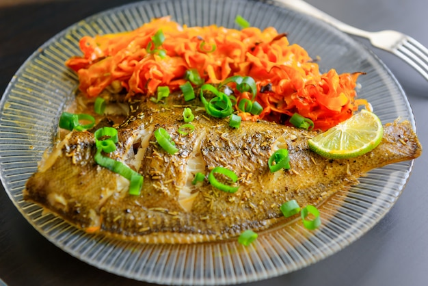 Baked fish flounder with lemon, carrot and spicy herbs, in a plate closeup on a black background. delicious fish dish with vegetables for healthy and proper nutrition.