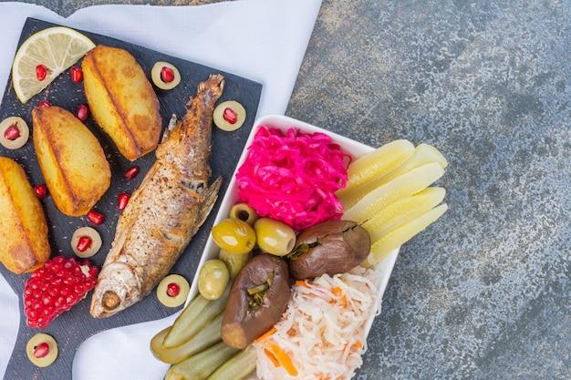 Pesce al forno e patate fritte su un tagliere accanto a una ciotola di conserve di verdure.