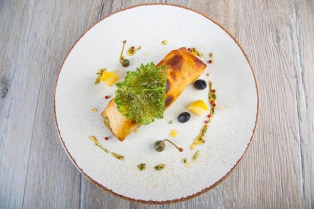 Запеченная рыба в тесте на белой тарелке с соусом песто