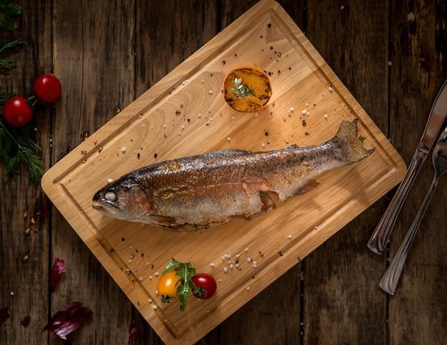 토마토와 레몬으로 장식된 도마에 구운 생선, 위쪽 전망