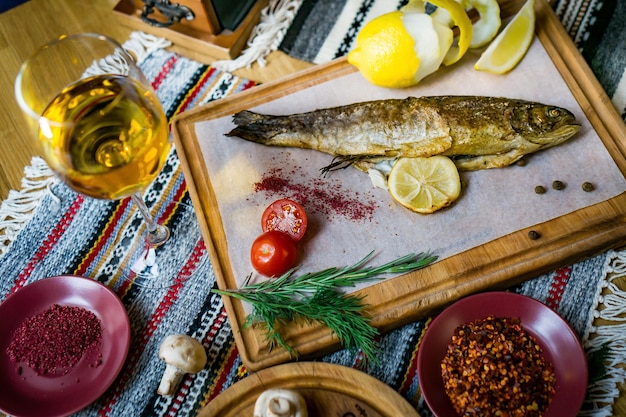 Baked fish seabass with fish spices, wine and salad. baked seafood in restaurant healthy eating