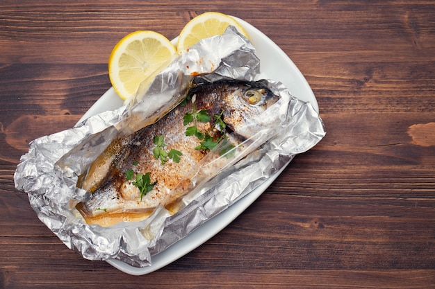 Baked fish with lemon in aluminium foil on wooden table