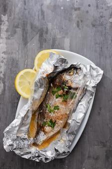 Baked fish with lemon in aluminium foil