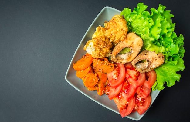 暗い背景に野菜と焼き魚