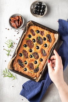 Baked focaccia with tomatoes, black olives and rosemary. natural italian homemade bread. top view.