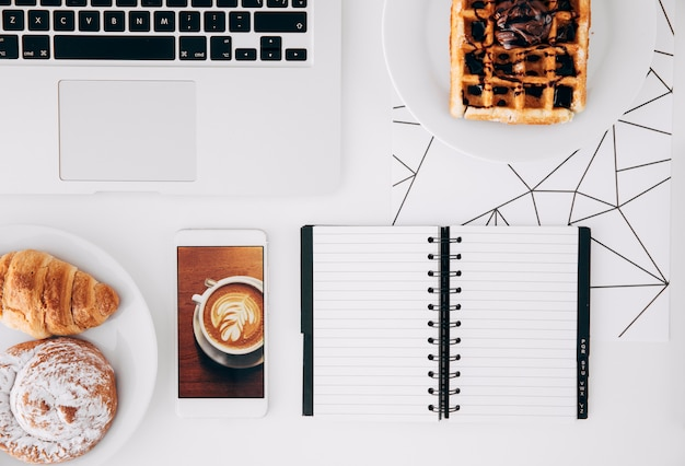 Baked food; chocolate waffle; mobile phone with coffee screen; laptop and spiral notepad on white desk