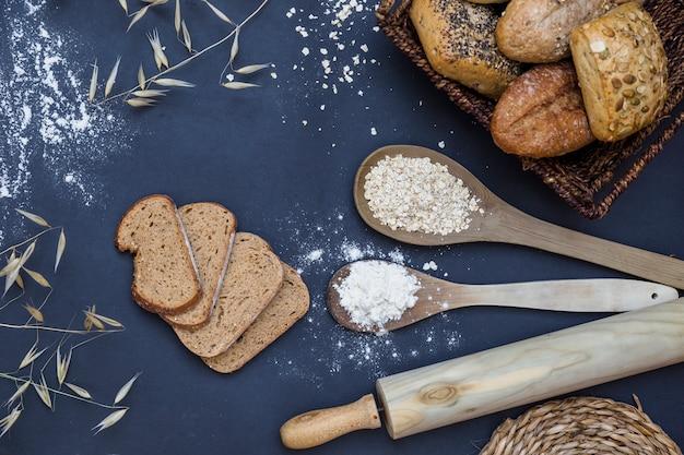 焼きたての食糧、キッチンのワークトップに小麦粉とオート麦のスプーンを入れたローリングピン