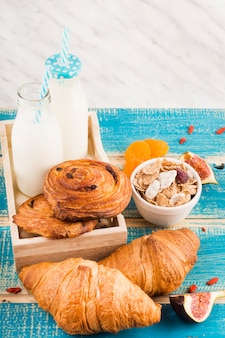 Baked food with milk bottles; bowl of corn flakes fig fruit slices and dry apricot over wooden desk