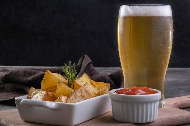 철 프라이팬에 로즈마리, 굵은 소금, 올리브 오일, 향신료 파프리카를 곁들인 구운 감자와 맥주 파인트.
