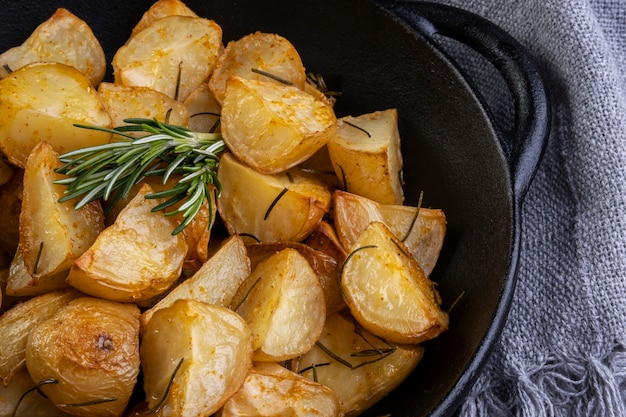 철 프라이팬에 로즈마리, 굵은 소금, 올리브 오일, 향신료 파프리카를 곁들인 구운 감자.