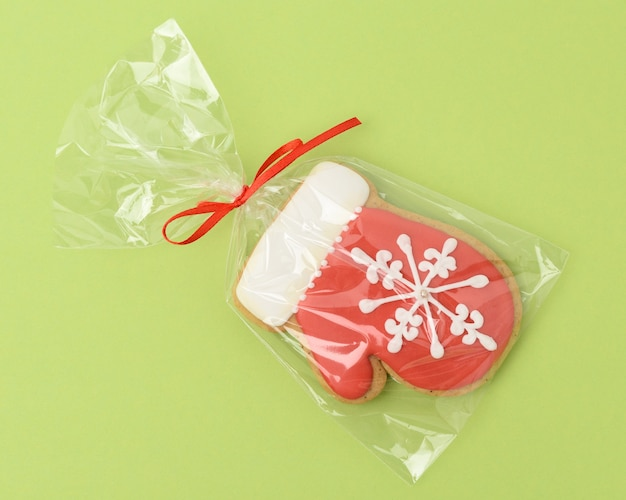Baked gingerbread in the shape of a mitten and covered with red icing,  classic christmas dessert