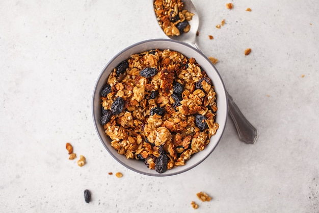 Baked granola with raisins in bowl, white background.