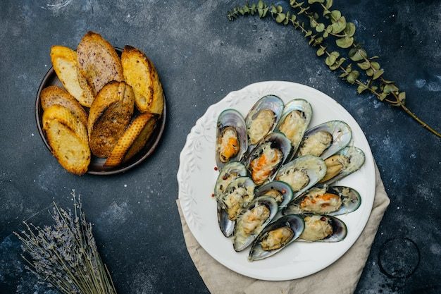 Baked green mussels with parmesan and garlic croutons on a white plate on a dark table