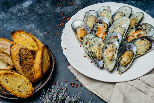 Baked green mussels with parmesan and garlic croutons on a white plate
