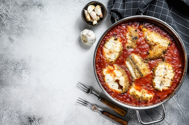 Baked grenadier macrurus white fish with tomato in a pan. white wooden background. top view. copy space.