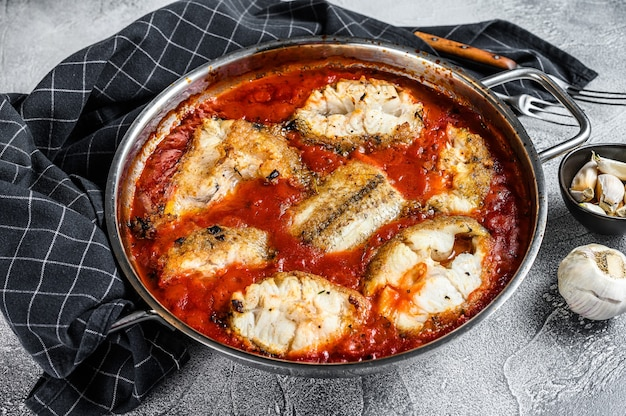 Baked grenadier macrurus white fish with tomato in a pan. white wooden table. top view.