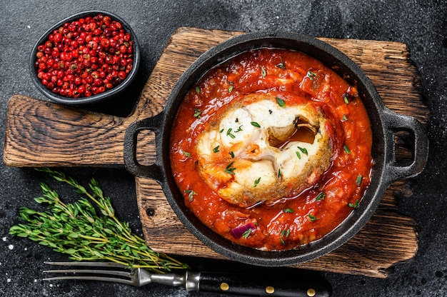 Baked hake white fish with tomato in a pan. black background. top view.