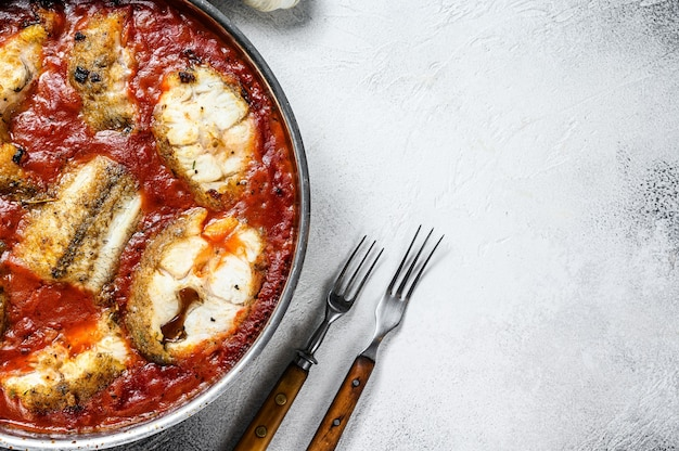 Baked hake white fish with tomato in a pan. white wooden table. top view. copy space.