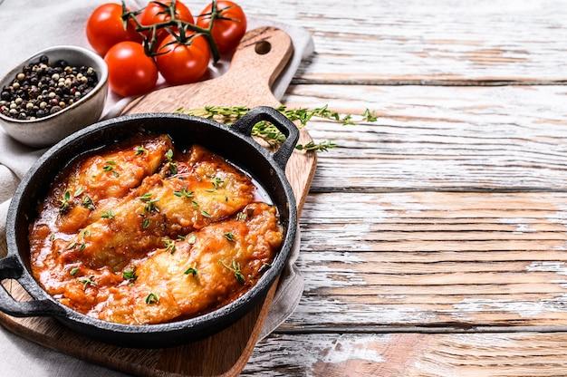 オヒョウの魚をトマトソースの鍋で焼いた。白い木製の背景。上面図。コピースペース。