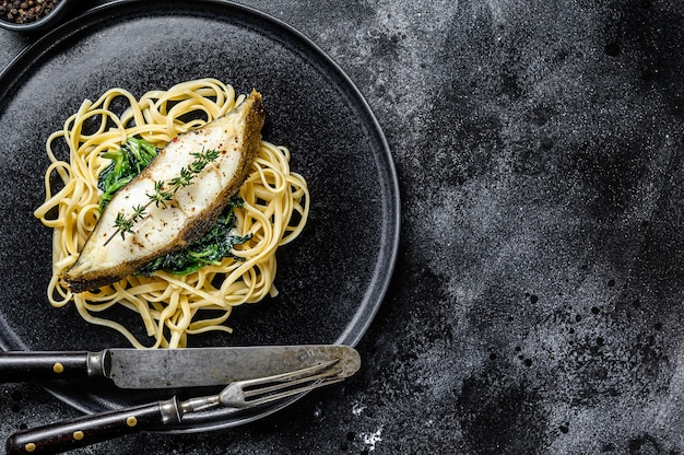 Запеченный рыбный стейк из палтуса и паста «спагетти» со шпинатом.