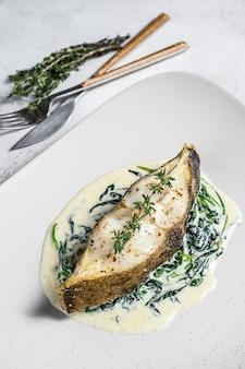 Запеченный рыбный стейк из палтуса со шпинатом.