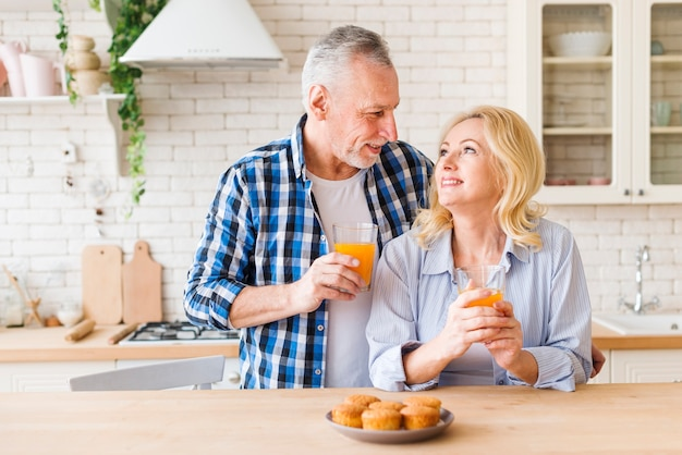 Baked homemade muffins on table in front of lovely smiling young couple in the kitchen