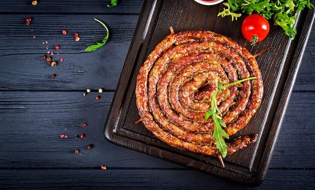 Запеченная домашняя колбаса на деревянной доске.