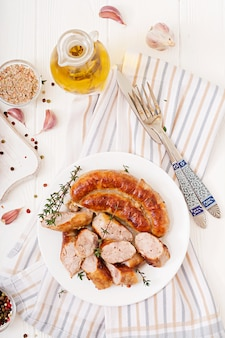 Baked homemade sausage on a white plate. thanksgiving day. top view