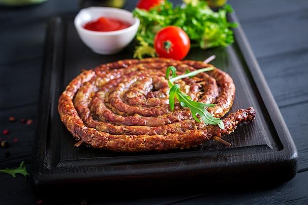 Salsiccia fatta in casa al forno su una tavola di legno.
