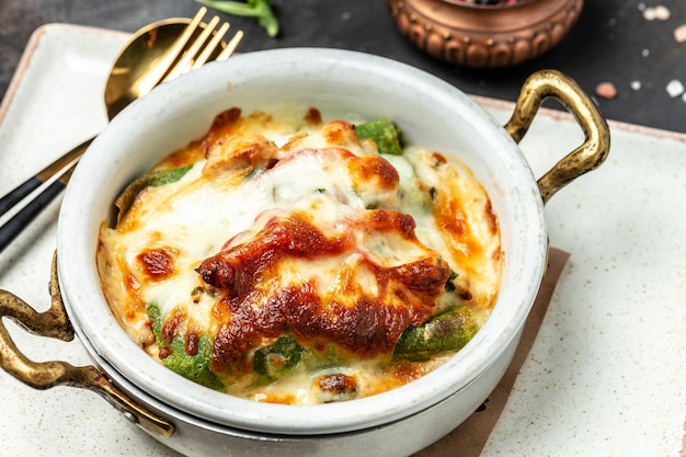 Запеченные горячие блинчики из шпината с курицей, сыром, грибами и соусом бешамель. предпосылка рецепта еды. закройте вверх.