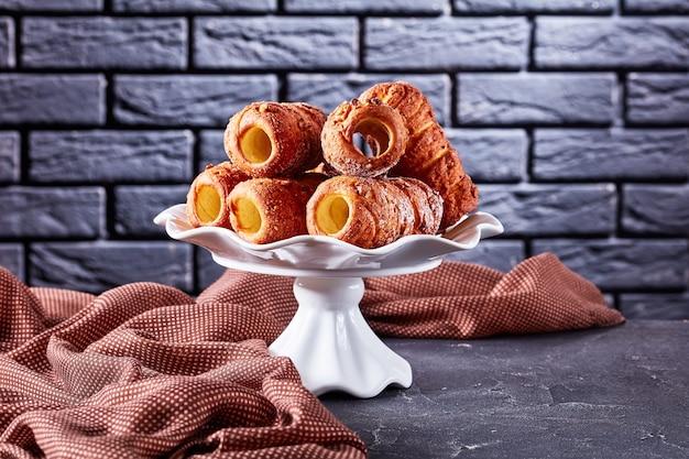 焼きたてのハンガリーのペストリーの煙突のケーキまたはkurotskalacsは、暗いコンクリートの背景に白い立っているプレートで提供されます