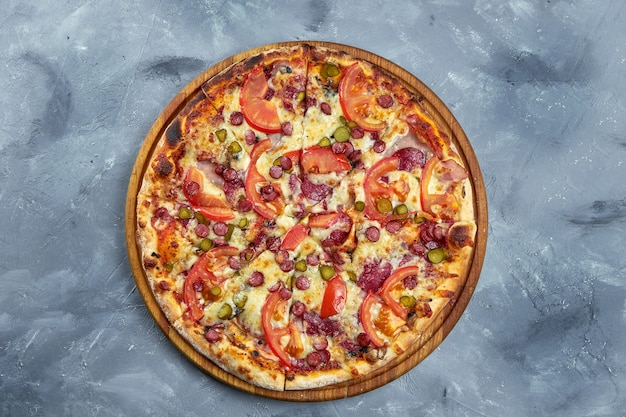 Baked italian pizza with smoked sausages, pickled cucumbers, salami and tomatoes on a wooden tray on a gray background.