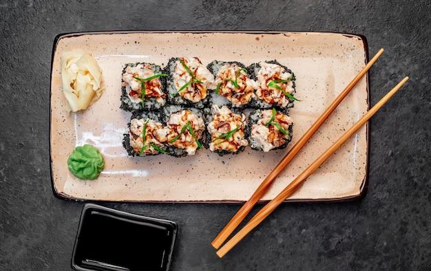 Запеченные японские суши роллы на каменном фоне