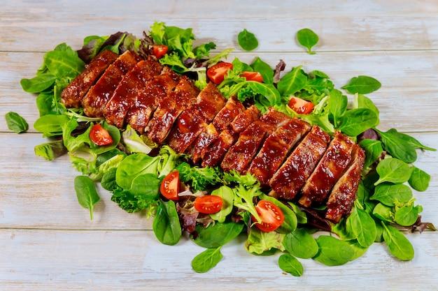 Запеченные сочные говяжьи ребрышки барбекю с соусом барбекю и салатом.
