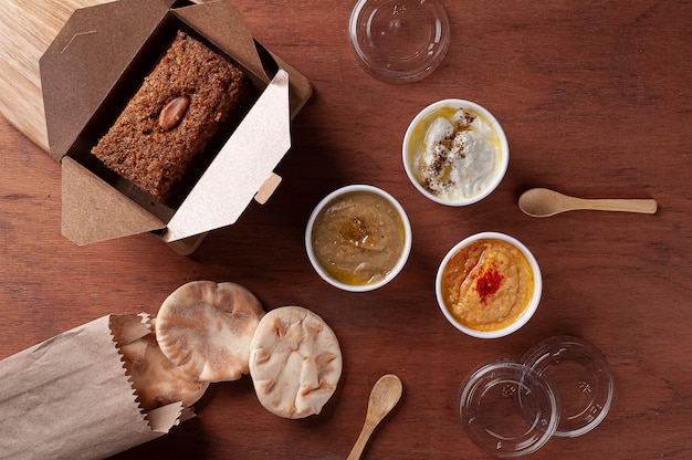 Baked kebab with side dishes, hummus, babaganoush, curd and pita bread. arabic food. delivery packaging. top view