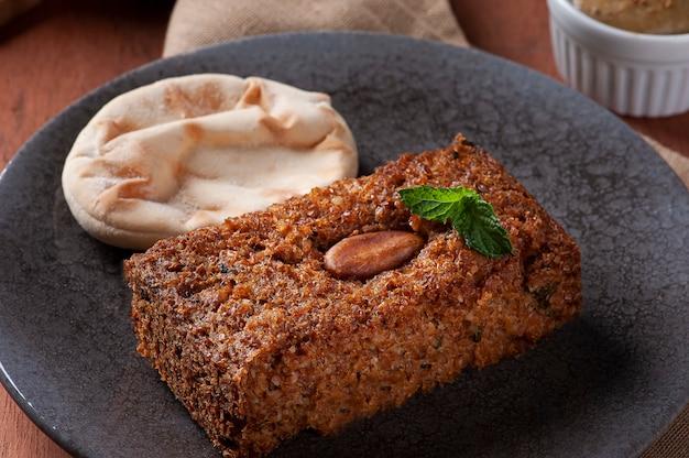 Baked kebab with side dishes, hummus, babaganoush, curd and pita bread. arabic food.