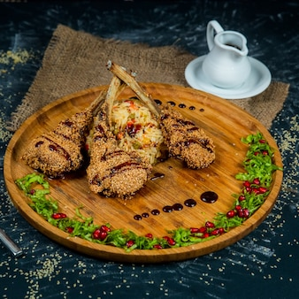 Baked lamb ribs with rice on a wooden round plate on a dark textured background