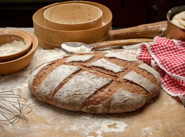 Буханка хлеба на столе и ингредиенты, посуда лежат рядом, вид сверху