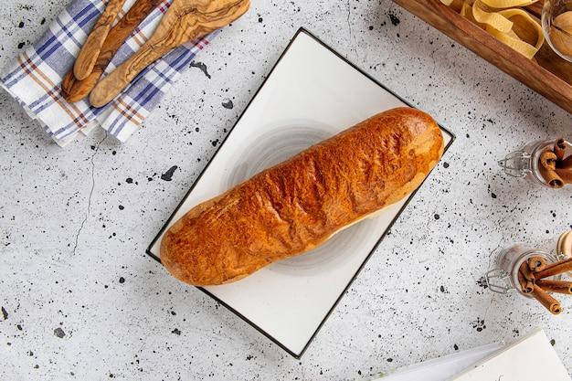 Запеченная длинная булочка на сервированном столе