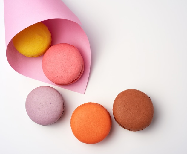 Baked macarons in a pink paper bag